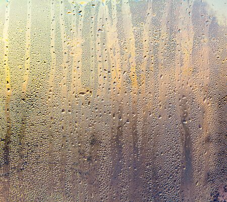 A foggy window at sunset as an abstract background. Imagens