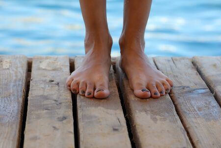 Legs of a girl on a wooden floor and a view of the blue sea.