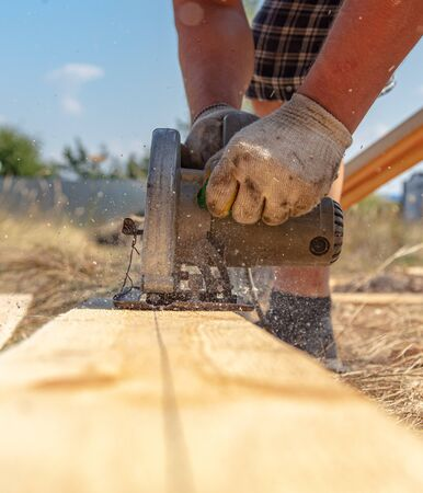 A worker cuts a wooden board at a construction site. Stockfoto