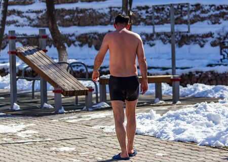 A man in swimming trunks in the winter.