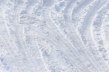 Traces of a car on white snow as a background. Banco de Imagens - 131357041