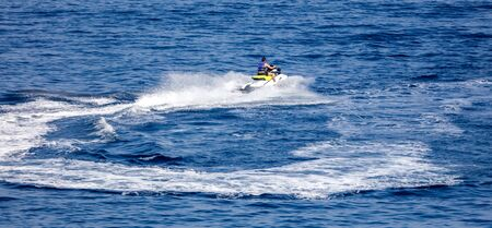 A motorcycle is racing in the blue water of the sea.