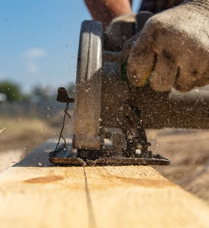 A worker cuts a wooden board at a construction site. Stock fotó