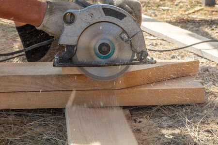 A worker cuts a wooden board at a construction site.