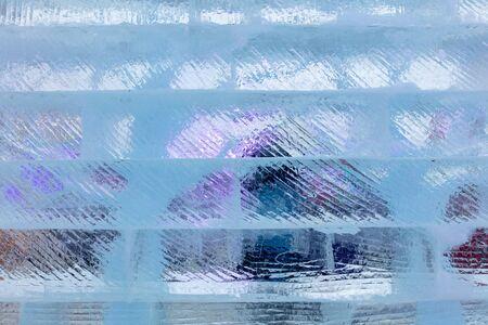 Ice bricks backlit in blue as a background. Фото со стока