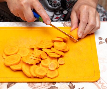 Woman cuts carrots with a knife on the board.
