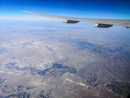 Airplane wing in flight. View from the porthole.