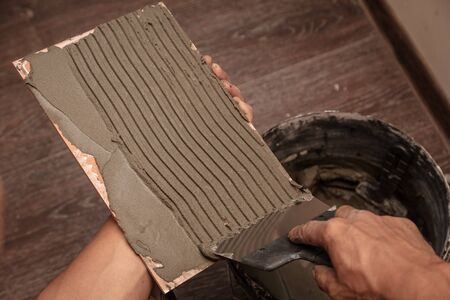 Worker glues tiles on the wall.