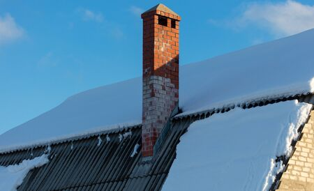 Brick house with snow on the roof in winter. Stock Photo