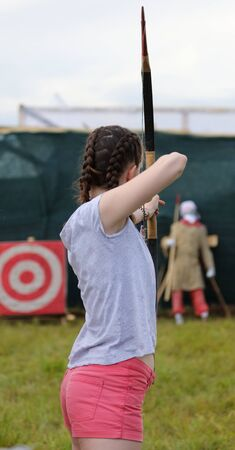 A girl shoots arrows from a bow.
