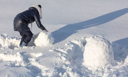 Girl sculpts a snowman in the snow in winter. Banque d'images - 133780834