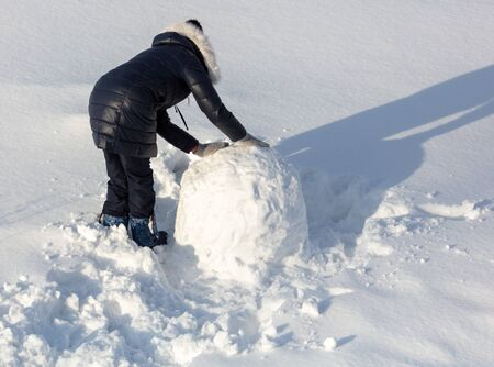 Girl sculpts a snowman in the snow in winter. Banque d'images - 133780844
