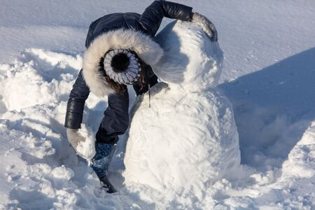 Girl sculpts a snowman in the snow in winter. Banque d'images - 133780851