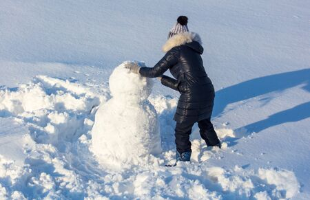 Girl sculpts a snowman in the snow in winter. Banque d'images - 133780855