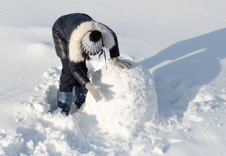 Girl sculpts a snowman in the snow in winter. Banque d'images - 133781032