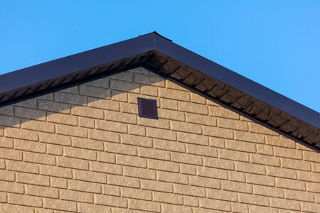 Roof in a brick house on a background of blue sky. Stock Photo