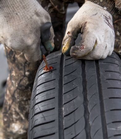 Elimination of a puncture on a car wheel. 스톡 콘텐츠
