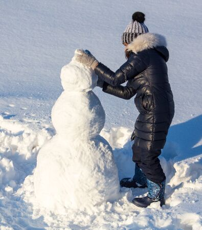 Girl sculpts a snowman in the snow in winter. Banque d'images - 133781682