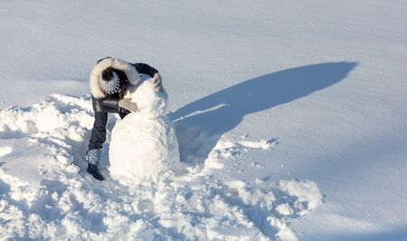 Girl sculpts a snowman in the snow in winter. Banque d'images - 133782099