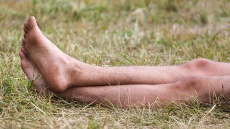Bare feet of a man on the grass.