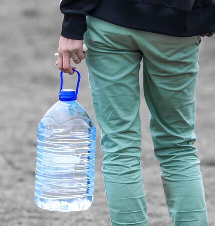 Plastic bottle with water in a man's hand. Foto de archivo - 133742916