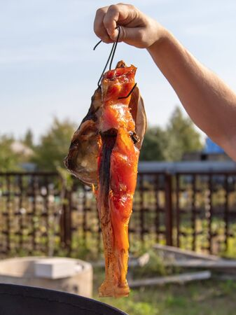 Smoked fish in a mans hand.