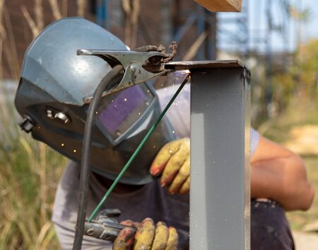Worker welds metal at a construction site.
