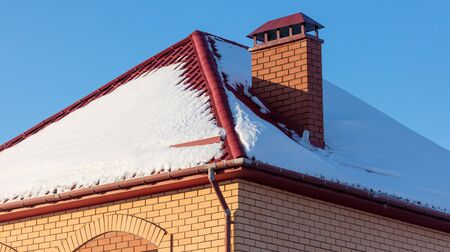 Brick house with snow on the roof in winter. Foto de archivo