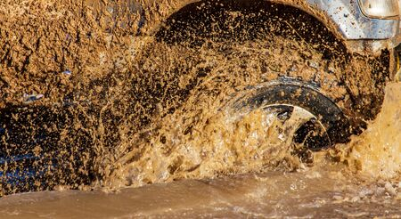 SUV wheel stalled in mud and water. Imagens