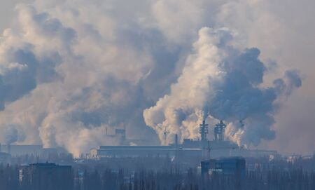 Smoke from the chimneys of a metallurgical plant at dawn.