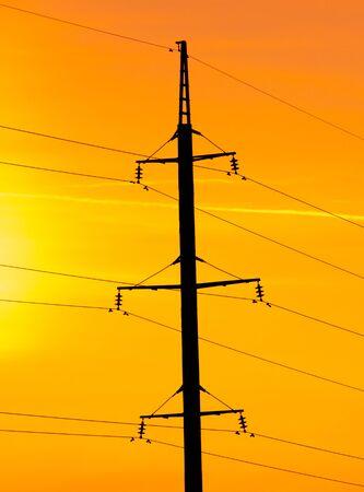 Poste eléctrico con cables sobre un fondo de puesta de sol. Foto de archivo