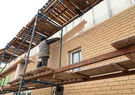 Installation of siding on the walls of the house. Construction worker