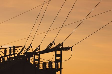 Silhouette of electrical substation at sunset.