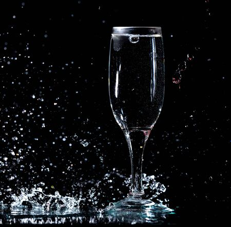 blue water with splashes in a glass on a black background.