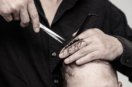 Hairdresser cuts the hair of a boy with scissors. Stok Fotoğraf