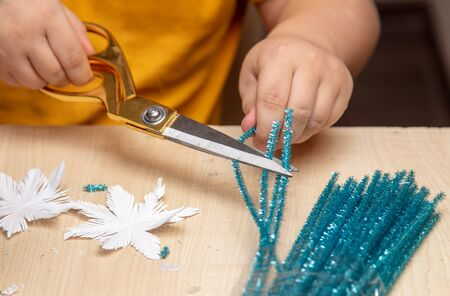 A boy glues snowflakes on a Christmas tree. Stock Photo