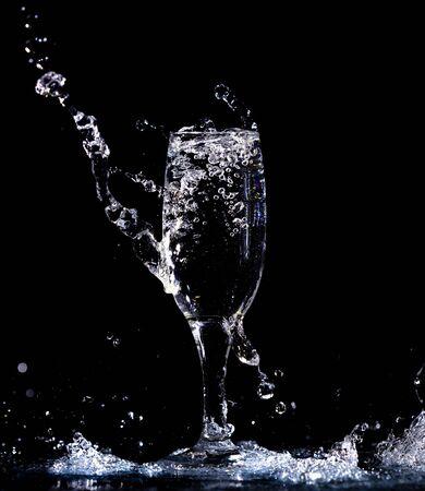 Acqua con spruzzi in un bicchiere su sfondo nero.