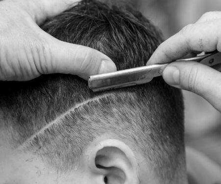 The hairdresser cuts the boys hair with a razor. Stok Fotoğraf