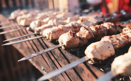 The meat on metal sticks is fried on the grill.
