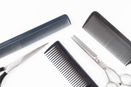 Scissors and combs for cutting hair on a white background.