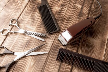 Scissors and combs and a clipper on a wooden background.