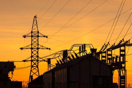Silhouette der Umspannstation bei Sonnenuntergang.