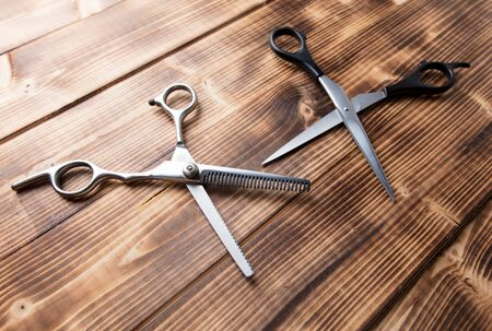 Scissors for haircuts on a wooden background. Фото со стока
