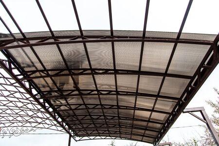 Un ouvrier monte un auvent en métal dans la cour de la maison. Vue de dessous de l'homme silhouette. Banque d'images