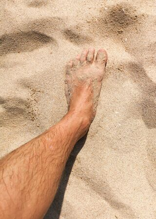 Feet of a man in the hot sand of the desert.