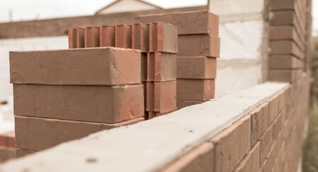 Bricks on a house under construction. Cottage village