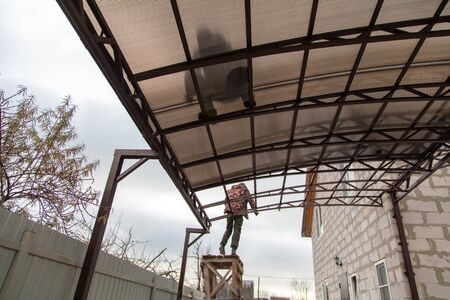 A worker mounts a metal canopy in the courtyard of the house. Silhouette man bottom view.