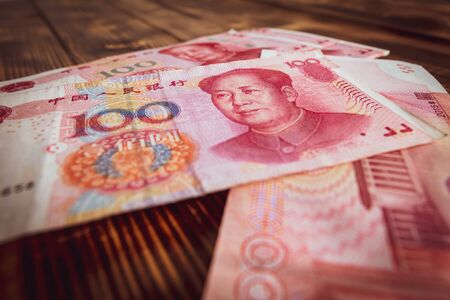 One hundred Chinese yuan on a wooden background.