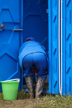 A cleaning lady cleans the toilets in the park. 스톡 콘텐츠