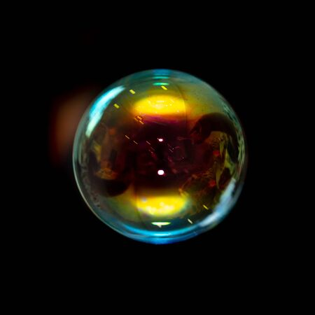 Multicolored soap bubble isolated on a black background.